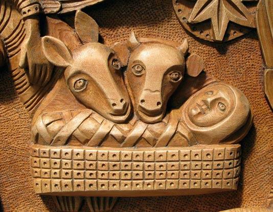 La sculpture de la Nativité du Christ avec une vue en détail de l'Enfant-Jésus, l'âne et le boeuf par le sculpteur sur bois Philippe Péneaud